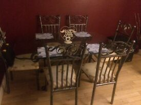 6 seater raw iron dining table. Glass top. Padded seats