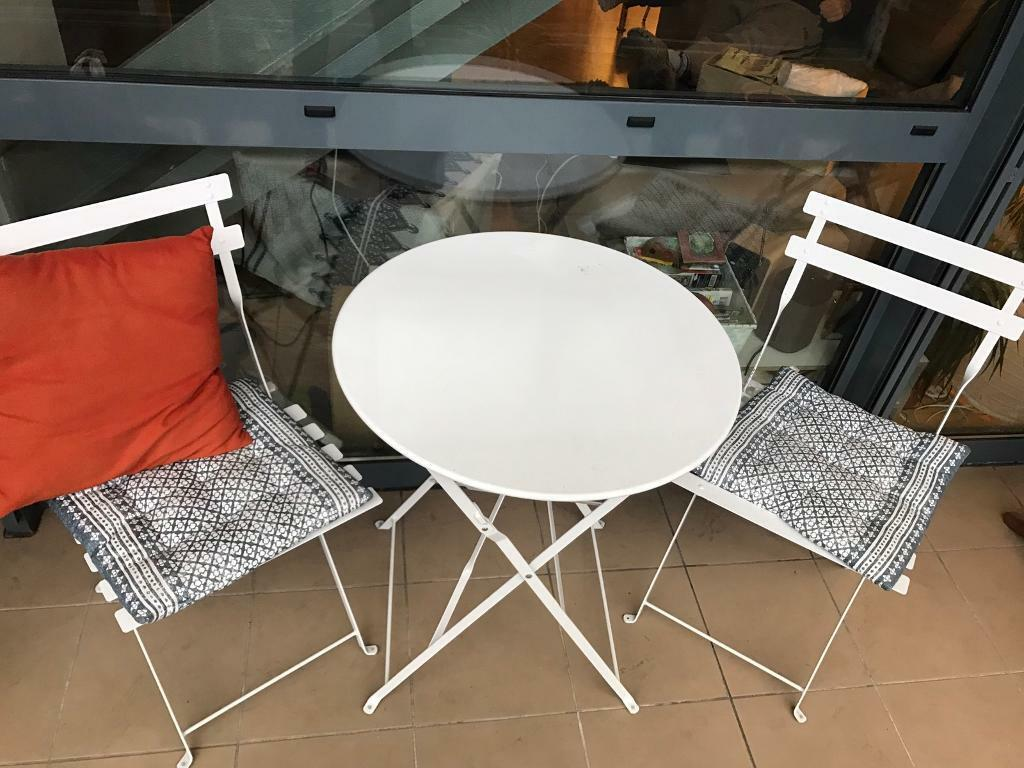 Outdoor table and chair bistro setin Salford, ManchesterGumtree - Round table and chair set (3 items) White metal, foldable and adaptable Bought from HomeSense for £49 last year Perfect condition Seat cushions and orange cushion is optional Looking to sell this week as Im moving country Pick up from my flat on...