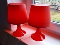 2 red Ikea plastic lamps with bulbs.