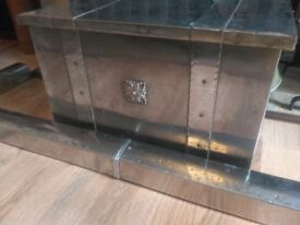 A silver coal box and matching fire place surround
