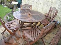 Garden table & 4 chairs fold away, heavy wood, good condition. With seat cushions.