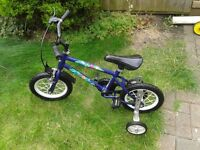 Child's first bicycle with stabilisers. Solid wheel and constant pedal.