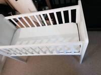 Baby crib with mattress and white sheet