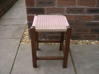 A wood framed footstool with woven cord seat.