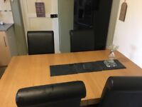 Oak dining table and 4 black leather chairs.