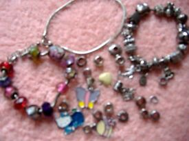 A collection of beads and bracelets in white metal, enamel and glass.