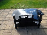 Black glass TV stand. Good condition.