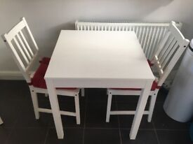 White square Ikea table with chairs and cushions