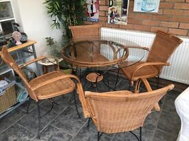 Circular glass top dining table and four wicker chairs