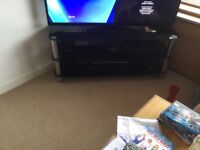 Black glass and silver tv and dvd stand with two shelves , good condition