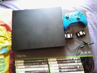 1tb boxed xbox one x with a blue wireless controller and 14 xbox 360 games