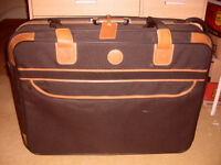 LARGE STURDY SUITCASE BY D IN BLACK AND TAN ON WHEELS