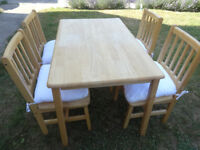 Solid rubberwood dining table with four chairs and cushions