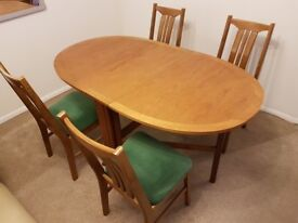 Wooden, pine, foldable dining table with four matching chairs.
