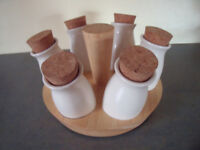 6 cream coloured ceramic spice/herb jars with cork stoppers in rotating/revolving wood rack. £5 ovno