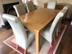 Solid oak dining table, 6 cream leather chairs, matching sideboard and lamp table. As new.