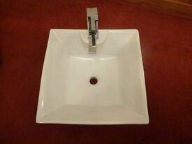 White bath and matching basin with tap.