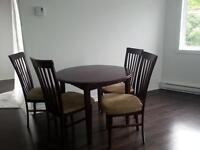 table ronde en bois avec quatre chaises et deux rallonges
