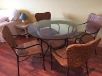 Beautiful round wrought iron, glass and rattan table with four chairs