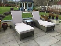 A pair of Rattan sun loungers complete with glass topped table and cushions