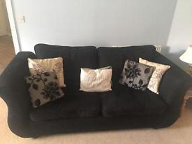 Black DFS three seater, two seater and foot rest
