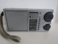 AM/FM POCKET/PORTABLE RADIO WITH CLOCK AND ALARM. WORKS GREAT! WITH CARRY STRAP.