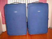 Two large identical blue TRIPP suitcases with two wheels and telescopic handles