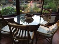 Glass table and four whicker chairs