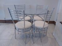 Glass and Stainless Steel dining table and chairs.