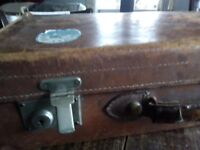 Vintage leather suitcase with destination stickers.