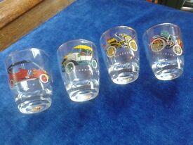 Four vintage shot glasses depicting vintage motor vehicles