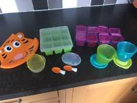 Mixture of weaning stuff including freezer pots, bib and pouch spoons