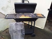 Large barrel style charcoal barbeque. Lid opens fully to allow cooking in both halves.