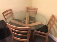 Solid oak and glass table with 4 oak chairs with black cushions