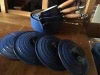 4 Blue Le Creuset sauce pans with lids and wooden handles.