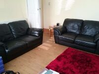 2 black leather two seater sofas