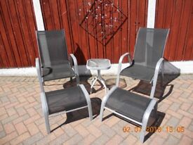 Two Chairs with foot stools and small glass table. Relaxing Patio Set