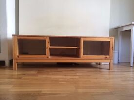 Wooden TV bench. £10 Glass doors Good condition -missing one small handle.Pick up from Central Btown