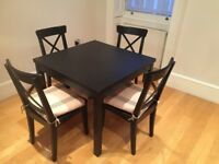 Extendable black IKEA Bjursta dining table with 8 chairs for £200, excellent condition (1yr old)