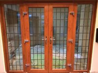 UPVC FRENCH DOORS AND SIDE PANELS IN GOLDEN OAK WITH RECTANGULAR LEADWORK.
