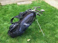A set of assorted kids golf clubs in golf bag