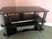 Smoked glass tv stand, chrome uprights.