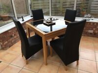 Dining table (extendable) with glass top and 4 chairs. Wood legs and surround.
