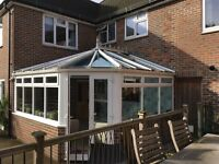 White corner UPVC conservatory with 2 roof openers
