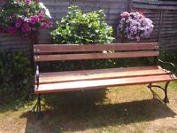 Handmade wooden garden bench with forged iron legs and armrests