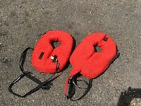2 children's life preservers and a paddle