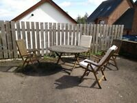 Solid wood garden dining set with 4 chairs and clean white cushions