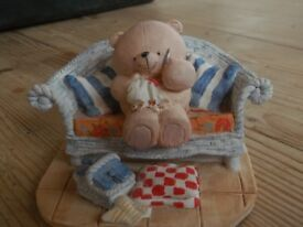 teddy on a sofa sewing