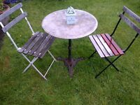 nicely weathered garden or patio cast iron table with marble top two folding chairs and lantern