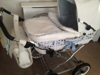 White wicker pram with blue ribbons and bows